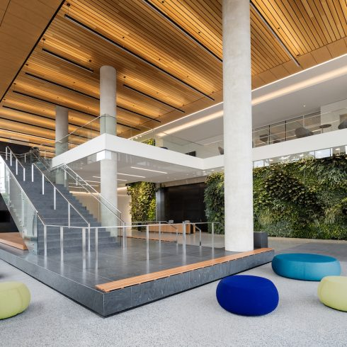 Wheaton HQ lobby staircase, green wall and blue and yellow seating